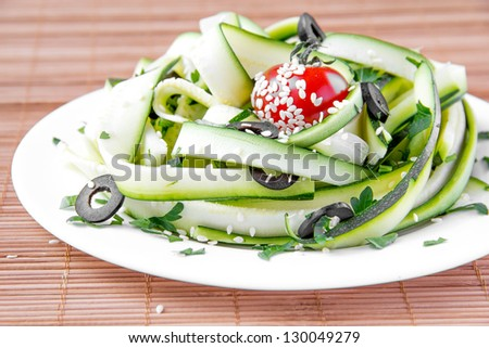 Salad from the zucchini ribbons, tomato and black olive - stock photo