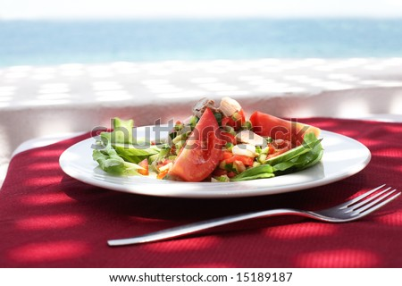 salad from tunny and fresh vegetables in restaurant on open air with sea view - stock photo