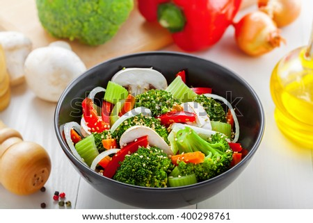 Salad in a bowl made of steamed broccoli, onion, mushroom, carrot and pepper.  Healthy vegetarian food.