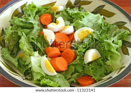 salad in a salad bowl on a butcher block table - stock photo