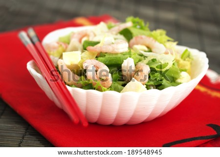Salad in seashell white plate made of green salad, avocado, green pepper, prawns and tofu cheese on red and black background with chinese sticks.
