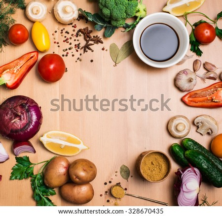 Salad ingredients on rustic wooden background with copy space, round frame, top view. Fresh vegetables mushrooms greens and spices around free copyspace. Healthy food concept. - stock photo