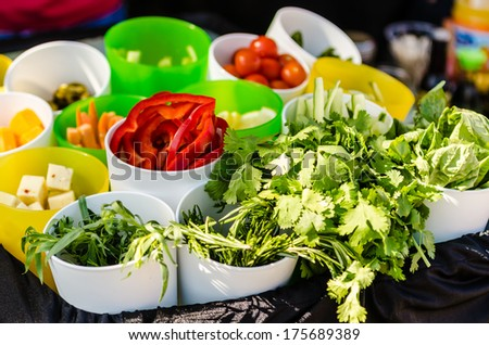Salad ingredients with lettuce, tomatoes, cucumbers, and cheese. - stock photo