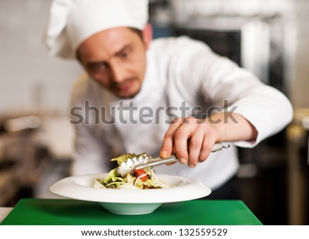 Salad is ready to be served. Chef ding last second decoration. - stock photo