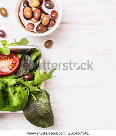 Salad leaves and olives on white wooden background - stock photo
