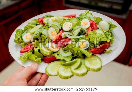 Salad. Lettuce, cucumbers, tomatoes, onions, quail eggs. Kitchen - stock photo