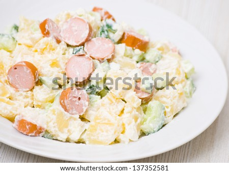 salad made of potato, cucumber, onion with mayonnaise dressing and sausage slices