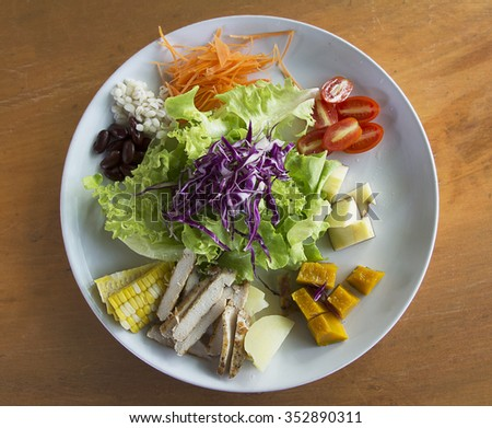 salad made with lettuce, tomatoes, cabbage, carrot, millet, red nuts, corn, potato, apple, pumpkin and chicken on plate, on wooden background - stock photo
