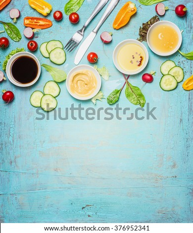 Salad making. Cutlery and dressing ingredients for fresh salad on light blue background, top view place for text. Vinegar ,mustard,oil and honey with chopped vegetables and lettuce leaves. - stock photo