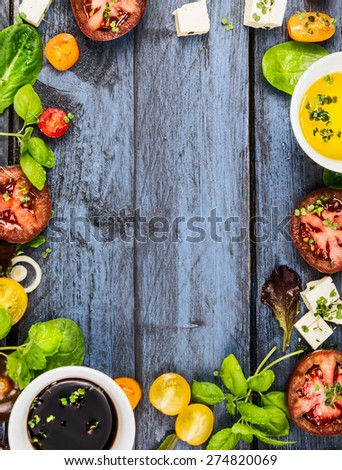 Salad making, food frame with oil,vinegar, tomatoes, basil and cheese on blue rustic wooden background, top view, vertical - stock photo