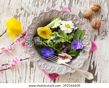salad mix with edible flowers in rustic spring  background