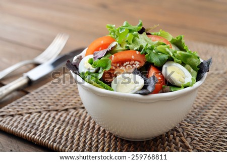 Salad mix with lettuce, tomato, cucumber and quail eggs in bowl on wooden background - stock photo