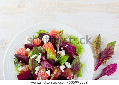 Salad of beets, lettuce, beetroot leaves, grapefruit and feta cheese on a light background. Top view. Place for text. Selective focus.