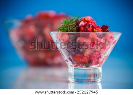 salad of boiled vegetables with beets on a blue background - stock photo