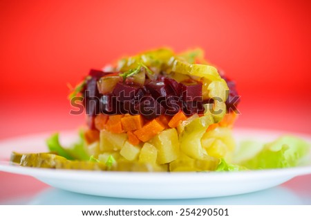 salad of boiled vegetables with beets on a red background - stock photo