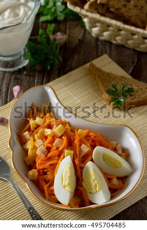 Salad of carrots, with cheese, egg and chicken meat on a wooden background.
