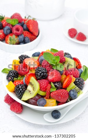 salad of fresh fruit and berries in a white bowl, berries and a cup of tea in the background, top view closeup - stock photo