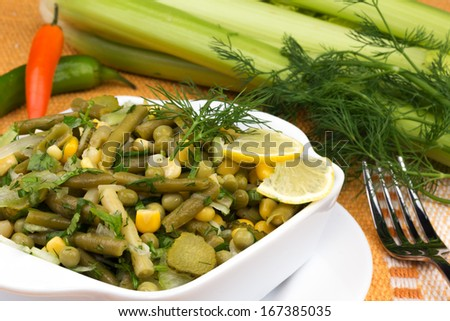 salad of fresh leek with green peas and green beans, greens on a plate - stock photo