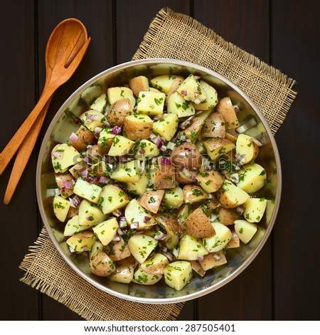 Salad of jacket potato, red onion and herbs in bowl with wooden spoon and fork, photographed overhead on dark wood with natural light - stock photo