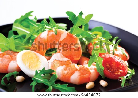 Salad of king prawns and rukola in a  black plate