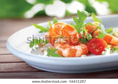 Salad of king prawns and rukola in a white plate