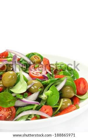 Salad of lamb's lettuce, olives, paprika, tomato and onion - stock photo