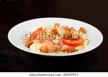 Salad of lettuce, Chinese cabbage, tomato, garlic rusk, parmesan cheese, sauce and smoked salmon filet - stock photo