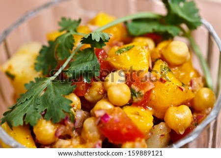 Salad of potato, chickpeas and mango??s tossed with tangy spices and fresh herbs  - stock photo