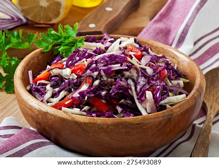 Salad of red and white cabbage and sweet red pepper, seasoned with lemon juice and olive oil in wooden  bowl - stock photo