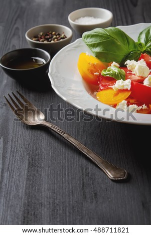 Salad of ripe tomatoes with basil and feta cheese on white teralke. Vegetarian food. Healthy breakfast. Dark wood background