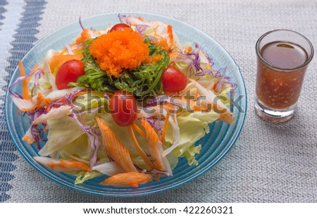 Salad of shrimps, crab meat, lettuce, aquatic weed, shrimp egg and tomato on dish - stock photo