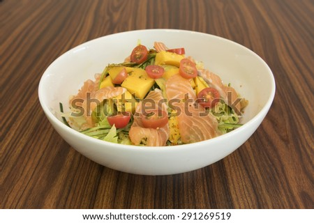 Salad of slices raw salmon and roe on fresh green vegetable with cucumber, cherry tomatoes, avocados and mangoes.  All ingredients are prepared and placed in layers in a large round white bowl.   - stock photo