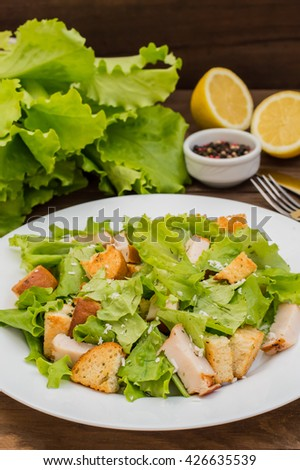 Salad of smoked chicken, croutons, lettuce and parmesan. Wooden rustic background - stock photo