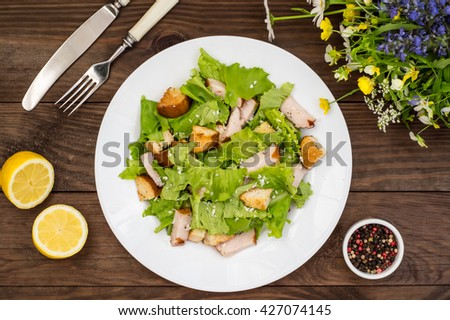 Salad of smoked chicken, croutons, lettuce and parmesan. Wooden rustic background. Top view - stock photo