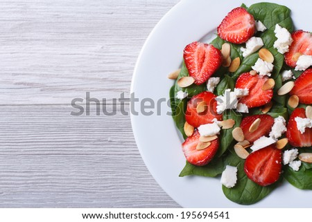 Salad of spinach, strawberries, cheese and almonds on the table top view close-up  - stock photo