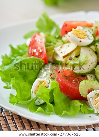 Salad of tomatoes, cucumbers and quail eggs - stock photo