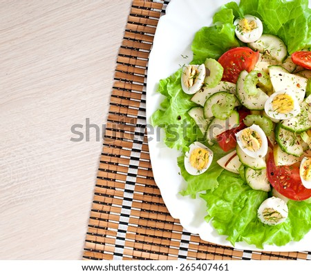 Salad of tomatoes, cucumbers and quail eggs. Top view. - stock photo