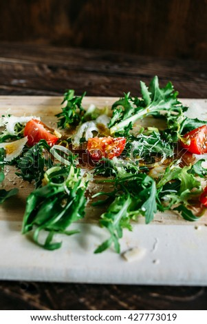 Salad on a brown background, arugula and tomato, arugula salad with tomatoes and parmesan, salad on a wooden board, salad  of arugula, salad with sesame seeds - stock photo