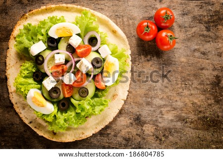 Salad on the tortilla bread with blank space on right side - stock photo