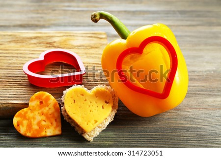 Salad pepper with cut in shape of heart and cheese on table close up - stock photo