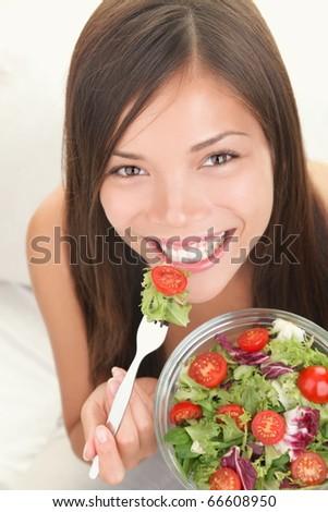 Salad. Portrait of healthy happy woman eating salad. Beautiful smiling Asian Caucasian female model. - stock photo