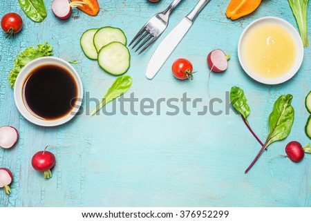 Salad preparation with cutlery dressing ingredients , lettuce , herbs and vegetables on light blue wooden background, top view, place for text. Healthy  lifestyle or detox diet food  concept - stock photo