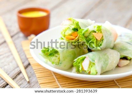 Salad roll vegetables with salad dressing in dish on wooden for Health - stock photo