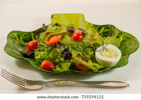 Salad, tomatoes, olives and egg on a plate