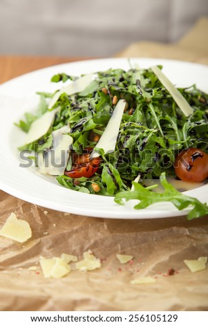 Salad with arugula and cherry tomatoes served on paper napkin on wooden table - stock photo