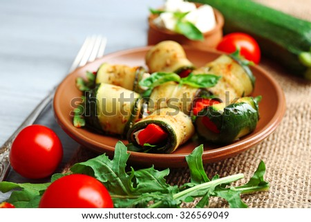 Salad with arugula and zucchini rolls on plate, on table background - stock photo