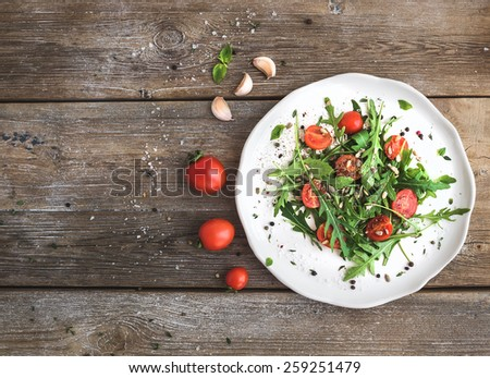Salad with arugula, cherry tomatoes, sunflower seeds and herbs on white ceramic plate over rustic wood background, top view, copy space - stock photo