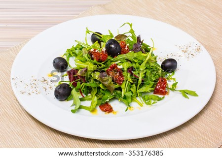 Salad with arugula, dried tomatoes and olives.