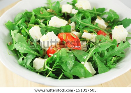 Salad with arugula, tomatoes, goat cheese and pumpkin seeds