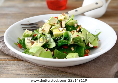 Salad with avocado and spinach in a white bowl, food close up